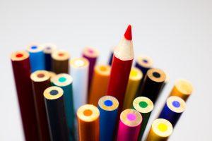 חבילת עפרונות צבעוניים ועיפרון אדום מחודד בולט