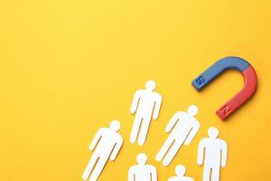 מגנט מושך אנשים מנייר על רקע צהוב