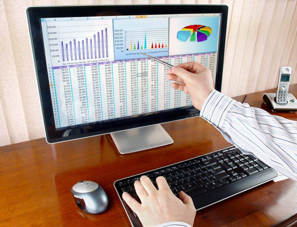 איש מצביע על מסך מחשב עם גרפים ומספרים