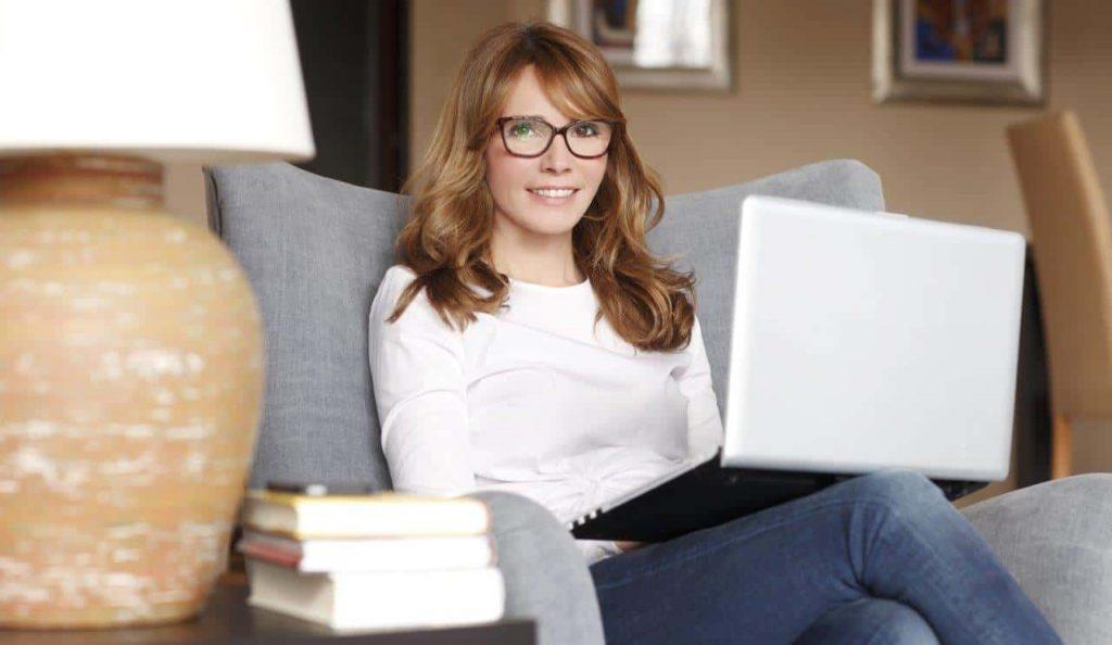 אישה יושבת בסלון עם לפטופ