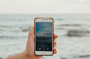 איש מחזיק טלפון ומצלם את הים