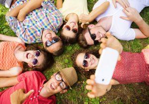 חברה צעירים מצטלמים על הדשא