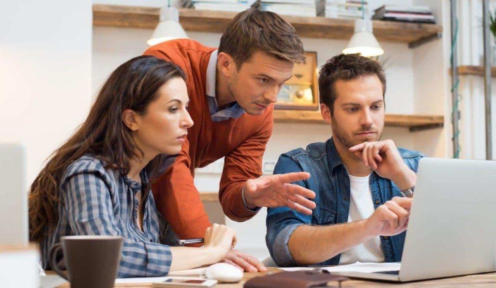 שלושה אנשי צוות חושבים ומסתכלים על לפטופ